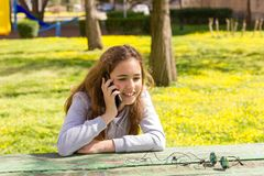 Menina bonita do adolescente com o smartphone m?vel do cellpfone no parque do ver?o fotos de stock