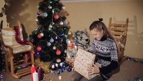 A menina bonita do adolescente perto de uma árvore de Natal abre uma caixa de presente com um presente do ` s do ano novo de Sant video estoque