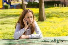 Menina bonita do adolescente que fala pelo smartphone m?vel do cellpfone no parque do ver?o imagens de stock