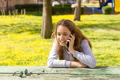 Menina bonita do adolescente que fala pelo smartphone m?vel do cellpfone no parque do ver?o imagem de stock