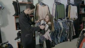 A menina bonita do adolescente que pergunta seu noivo em uma loja da compra se pode comprar a abundância dos panos e no ele disco vídeos de arquivo