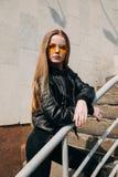 Menina bonita do adolescente do retrato da forma nos óculos de sol e estilo preto da rocha sobre o fundo da cidade imagens de stock royalty free