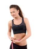Menina bonita do ajuste que mede sua cintura com uma fita de medição cor-de-rosa nos centímetros. Fotos de Stock