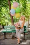 Menina bonita do aniversário com flores e os balões bonitos imagem de stock