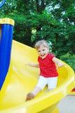 A menina bonita do campo de jogos está montando uma montanha russa. Imagem de Stock