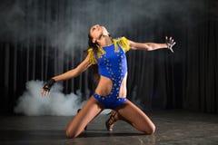 Menina bonita do dançarino em um assento azul do traje Fotos de Stock Royalty Free