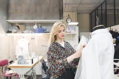 A menina bonita do desenhador de moda está em um estúdio perto do manequim e fixa a roupa nele imagem de stock