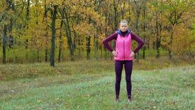 A menina bonita do esporte da aptidão aquece-se antes de correr no parque do outono Exercício fora filme