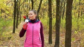Menina bonita do esporte da aptidão que anda ao longo do parque do outono no sportswear com garrafa de água dos esportes ou bebid video estoque