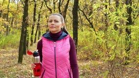 Menina bonita do esporte da aptidão que anda ao longo do parque do outono no sportswear com garrafa de água dos esportes ou bebid filme