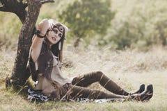 Menina bonita do estilo de Boho que descansa pela árvore na natureza Foto de Stock