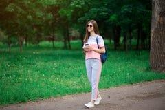 Menina bonita do estudante nos óculos de sol que bebe o café no parque fotos de stock
