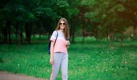 Menina bonita do estudante nos óculos de sol que bebe o café no parque imagem de stock