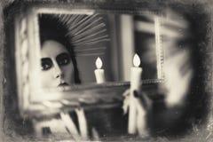 Menina bonita do goth que mantém a vela disponivel e que olha no espelho Efeito da textura do Grunge Foto de Stock Royalty Free