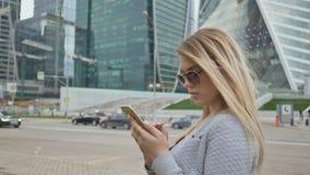 Menina bonita do louro no uso dos óculos de sol do telefone celular na perspectiva do centro da cidade filme