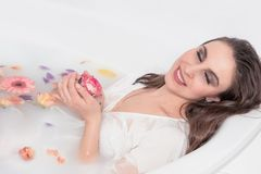 Menina bonita do modelo de forma com as rosas cor-de-rosa que tomam o banho do leite imagem de stock royalty free