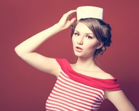 A menina bonita do pino-acima vestiu um marinheiro que levanta no fundo vermelho Imagens de Stock Royalty Free