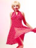 Menina bonita do pinup na peruca loura e na dança vermelha retro do vestido. Partido. Imagem de Stock