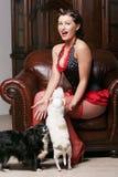 Menina bonita do pinup que joga com seus dois filhotes de cachorro fotografia de stock
