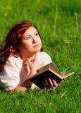 Menina bonita do Redhead que lê um livro na natureza Foto de Stock Royalty Free