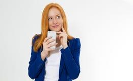 Menina bonita do ruivo com o sorriso do telefone isolado no fundo branco A fêmea foxy nova no equipamento do negócio, surpreendeu fotografia de stock royalty free