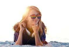 Menina bonita do ruivo com os fones de ouvido na areia da praia fotografia de stock royalty free