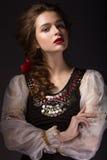 Menina bonita do russo no vestido nacional com um penteado da trança e os bordos do vermelho Face da beleza foto de stock