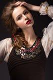 Menina bonita do russo no vestido nacional com um penteado da trança e os bordos do vermelho Face da beleza imagem de stock royalty free
