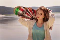 Menina bonita do skater que guarda o skate Fotografia de Stock