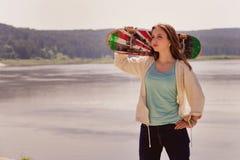 Menina bonita do skater que guarda o skate Imagem de Stock