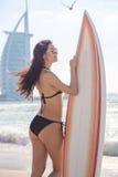 Menina bonita do surfista na praia no tempo do por do sol Foto de Stock