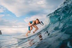 Menina bonita do surfista na prancha Mulher no oceano durante surfar Onda do surfista e do tambor fotografia de stock royalty free