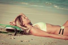 Menina bonita do surfista que encontra-se na praia imagens de stock royalty free
