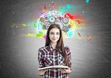 Menina bonita do totó com um livro e as rodas denteadas do cérebro foto de stock royalty free