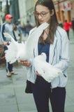 A menina bonita do turista guarda nos pombos brancos das mãos imagens de stock royalty free
