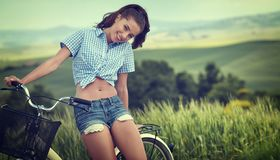 Menina bonita do vintage que senta-se ao lado da bicicleta, horas de verão fotos de stock royalty free