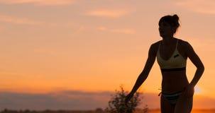 Menina bonita do voleibol em um biquini no antebraço do por do sol para passar sua colega de equipe durante um fósforo, filme