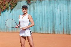 Menina bonita dos esportes com uma raquete de tênis em suas mãos Em um tampão preto Imagem de Stock Royalty Free