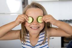 Menina bonita e adorável nova 6 ou 7 anos velha tendo a cozinha do divertimento em casa que põe fatias do pepino sobre seu sorris Fotografia de Stock