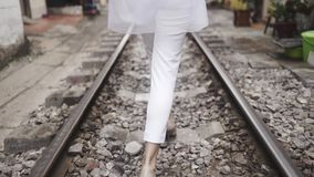 A menina bonita e elegante da forma que anda ao longo da estrada de ferro passa na rua O close up segue os pés viagem vídeos de arquivo