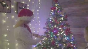 Menina bonita e mum que decoram a árvore de Natal na casa Família feliz filme
