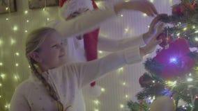 Menina bonita e mum que decoram a árvore de Natal na casa Família feliz video estoque