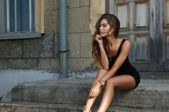 A menina bonita e 'sexy' nova com sol magro o corpo atrativo bronzeado vestido em uma camiseta interioa preta furtiva é levantar  imagem de stock