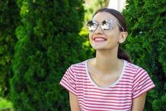 Menina bonita em óculos de sol cor-de-rosa sobre o fundo do parque foto de stock