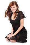 A menina bonita em brincos do vestido e da oferta senta-se no assoalho Imagens de Stock Royalty Free
