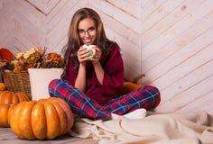 Menina bonita em casa nos pijamas Jovem mulher e abóboras bonitas Autumn Girl Fotos de Stock Royalty Free