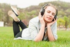Menina bonita em fones de ouvido vestindo do parque e descanso na grama fotos de stock royalty free