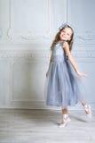 A menina bonita em sapatas cinzentas do vestido e do pointe está levantando no r Foto de Stock