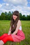 A menina bonita em sarafan vermelho senta-se na grama verde Foto de Stock