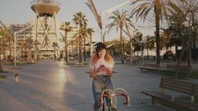 Menina bonita em sua bicicleta urbana do vintage no por do sol video estoque